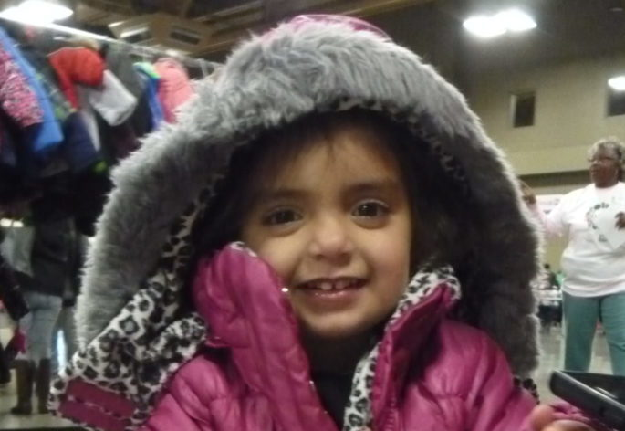 Young girl wearing puffy, pink coat at Coats for Kids