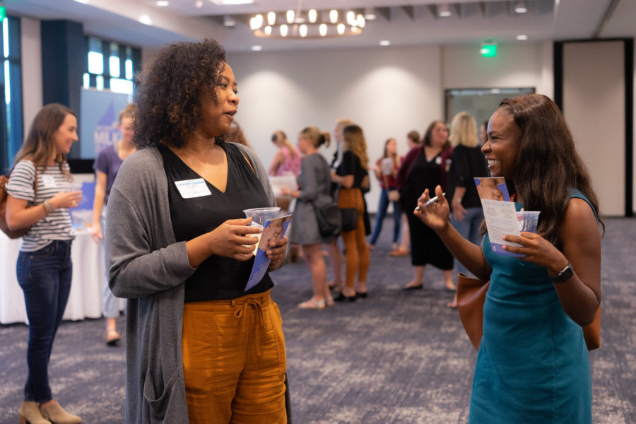 Two women visit and laugh at an admissions event